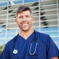 smiling-male-healthcare-worker-outside-hospital-resized.jpg
